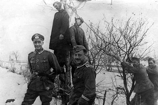 Немецкие солдаты фотографируются на фоне двоих повешенных советских партизан